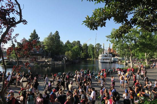 Crowds of people, and the Mississippi River Boat at  New Orleans Square in Disneyland