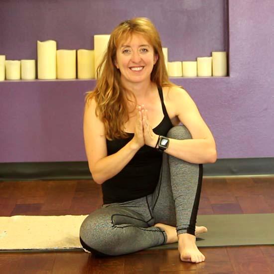 female yoga teacher sitting on yoga mat
