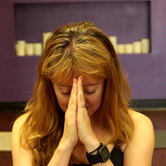 female yoga teacher bowing head with hands in prayer