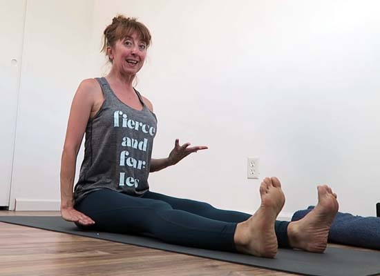 yoga teacher sitting in dandasana and hands not touching the floor