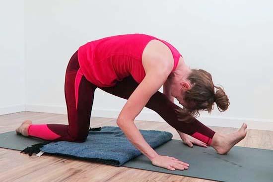 Yoga teacher folded into half split pose