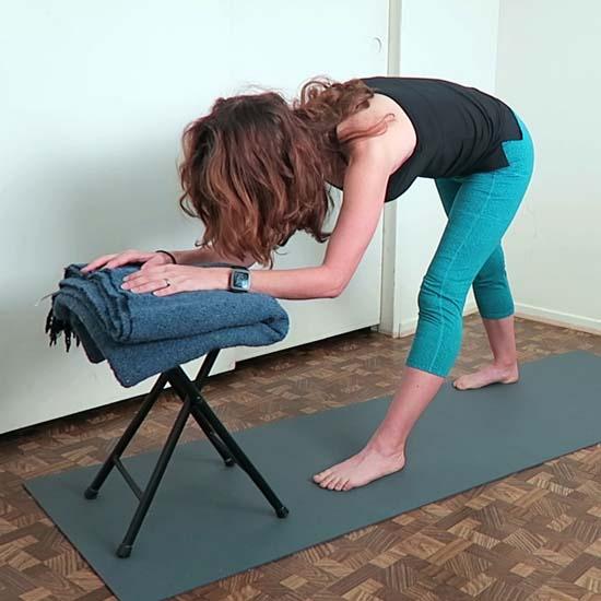 yoga teacher demonstrating pyramid pose using a chair