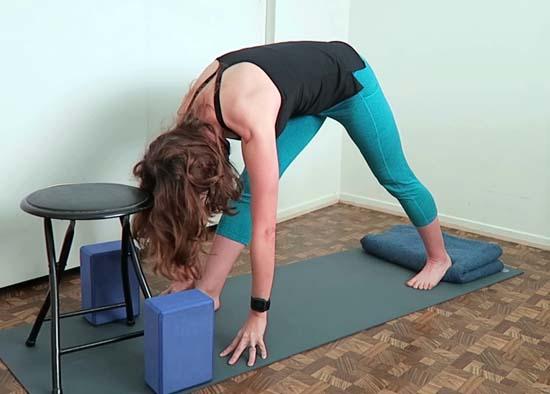 yoga teacher demonstrating pyramid pose using support