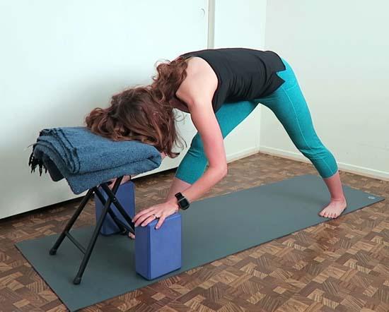 yoga teacher demonstrating pyramid pose using a chair and blocks