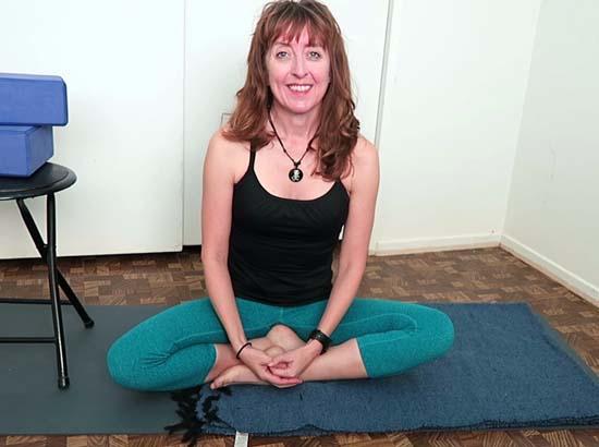 yoga teacher sitting in siddhasana on a yoga mat