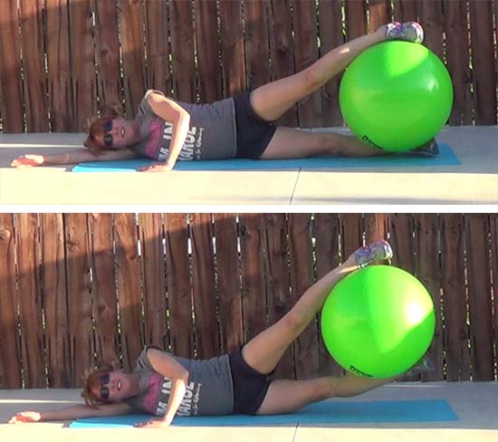 personal trainer performing lying leg lifts exercise with stability ball