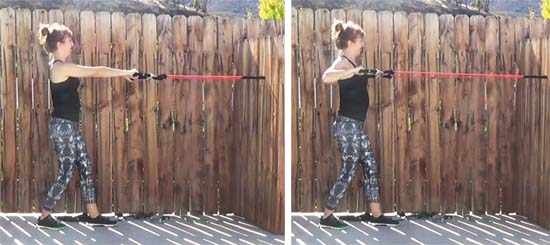 Personal trainer performing standing row with resistance band