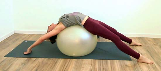 yoga teacher doing a full supported backbend on a stability ball