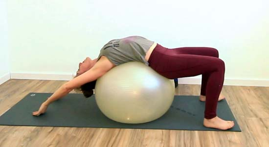 yoga teacher doing a backbend on a stability ball with knees bent and arms overhead