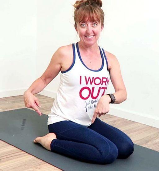 Yoga teacher demonstrating hero's pose with ankles on floor