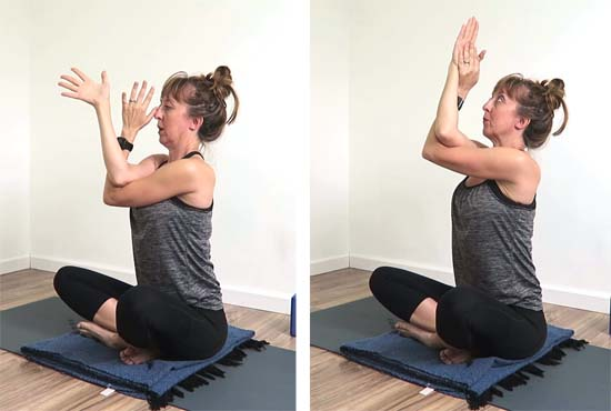 Yoga teacher demonstrating eagle arm modification with the forearms together and added wrist twist