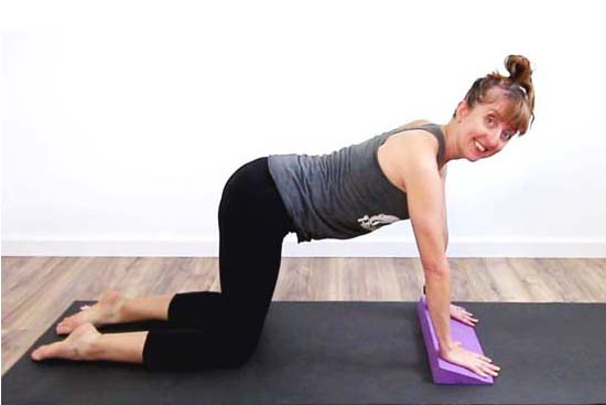 Yoga teacher using a yoga wedge under the hands to support the wrists