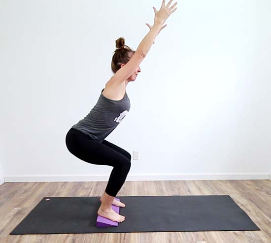 yoga teacher showing variation of chair pose standing on a yoga wedge