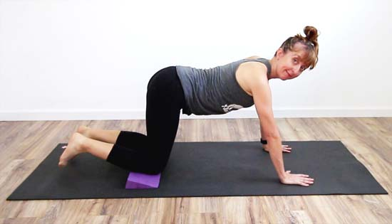 yoga teacher using wedge under the knees for support