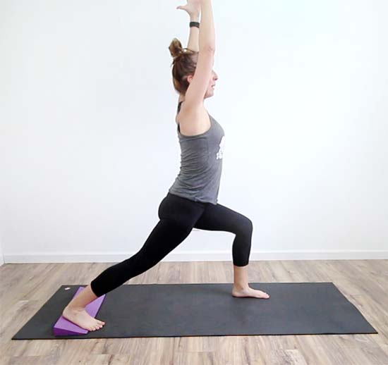 yoga teacher showing variation of warrior 1 with yoga wedge under the back foot