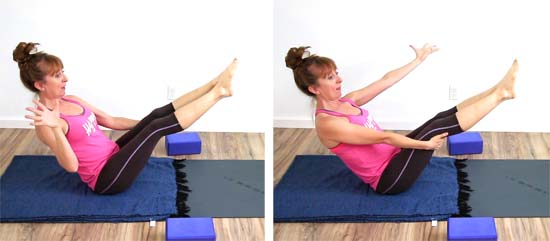 Yoga teacher holding boat pose with straight legs and  hands behind knees, releasing one hand at a time