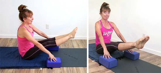 Yoga teacher performing dandasana double leg raises
