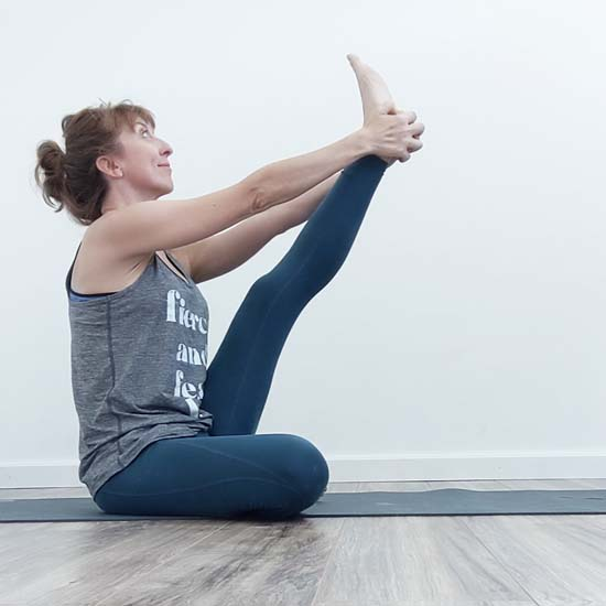 yoga teacher in heron pose