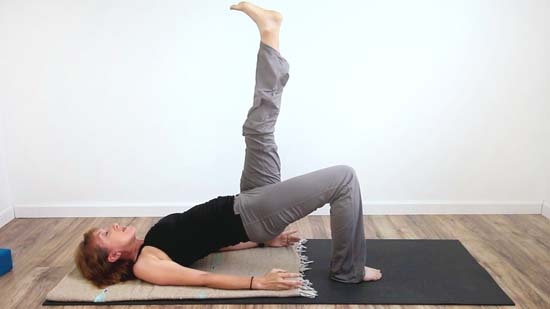 yoga teacher in single leg hip bridge exercise