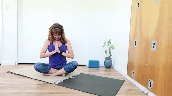 yoga teacher sitting on yoga mat with head bowed