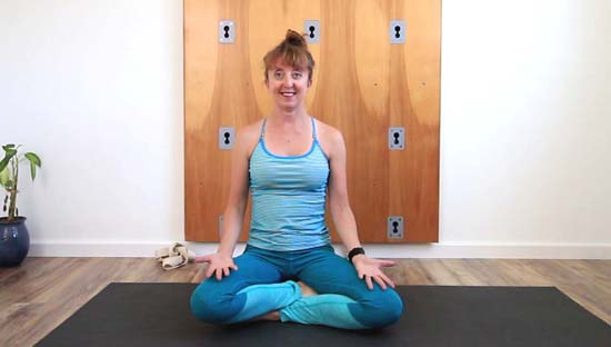 yoga teacher sitting in sukhasana using bolster/blocks