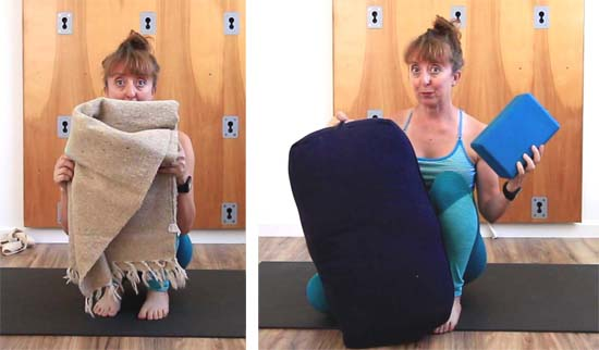 Woman holding blanket, yoga bolster and blocks