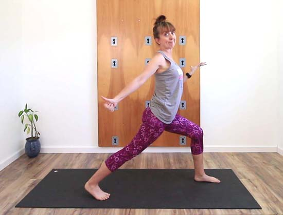 yoga teacher demonstrating warrior 1 with back heel elevated