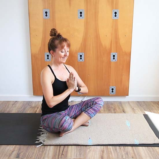 Di Hickman seated in sukhasana and hands in prayer position