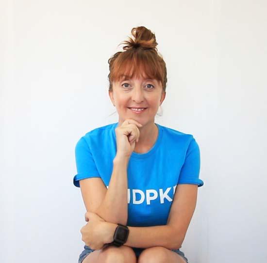 Di HIckman sitting wearing a teal t-shirt with #endpkd slogan