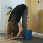 yoga teacher demonstrating standing forward fold