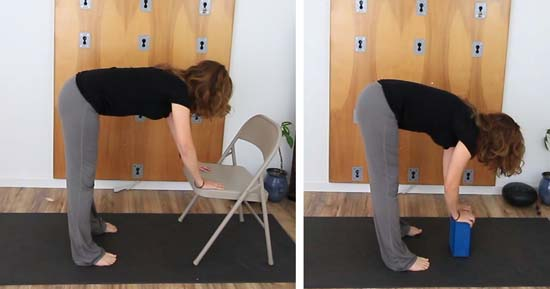 yoga teacher demonstrating forward fold with upper body supported