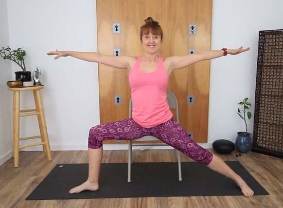 Yoga teacher seated in chair Warrior 2 pose