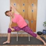 Yoga teacher seated in chair side angle pose