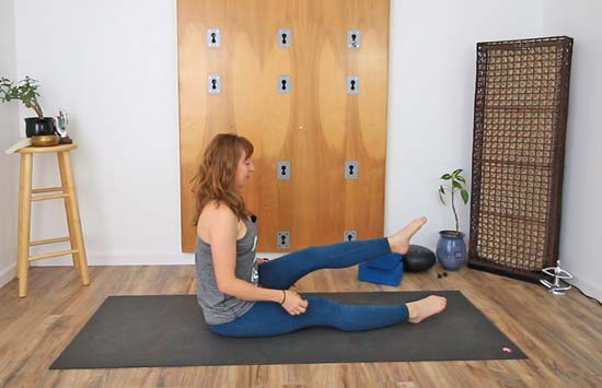 Seated on floor with legs extended in front, lifting one leg up