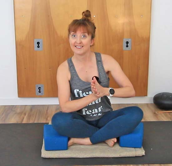 Sitting cross legged with legs supported on yoga blocks