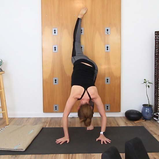 yoga teacher in a standing split against a wall