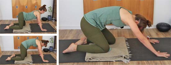 yoga teacher dressed in green on all fours on a  yoga mat