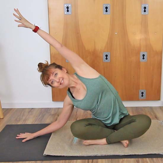 yoga teacher dressed in green seated on a  yoga mat reaching one arm up and over to the opposite side