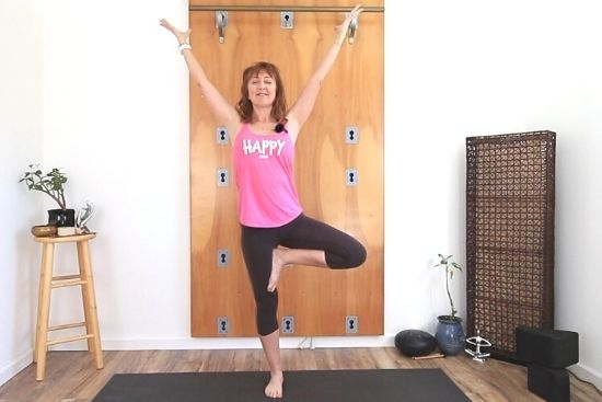 tree pose with arms lifted and eyes closed