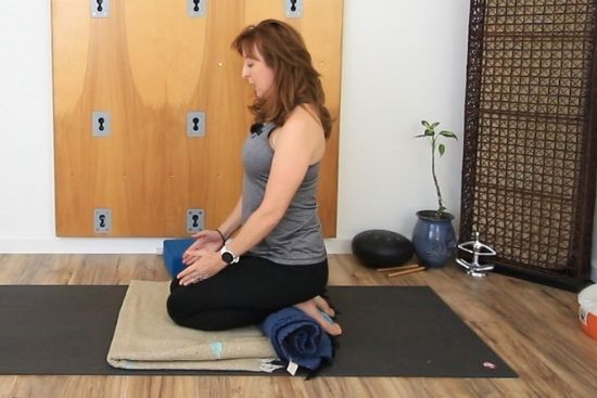 vajrasana with rolled blanket under the ankles