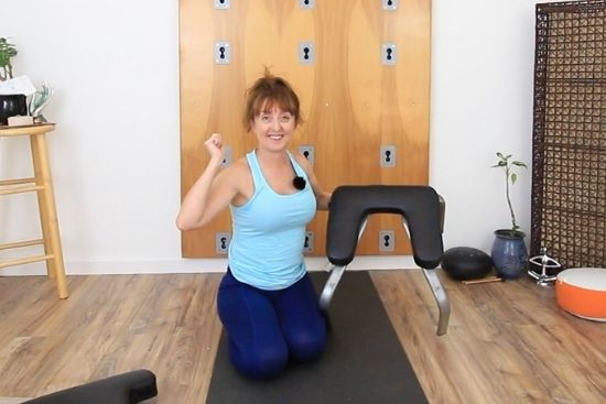 yoga teacher with headstand bench