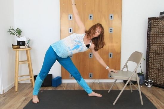using a chair for support in triangle pose