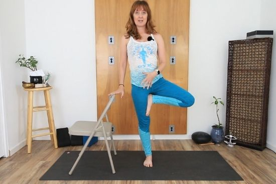 using a chair for balance in tree pose