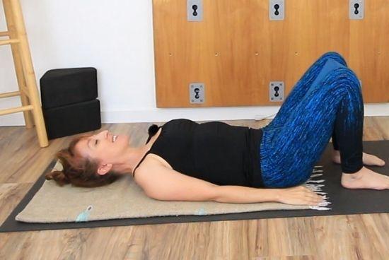 lying on back with yoga block between legs