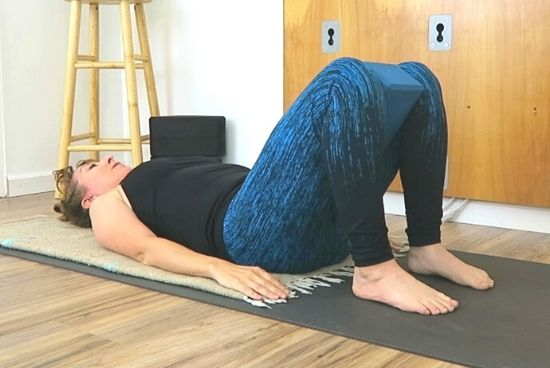 lying on back with yoga block between inner thighs